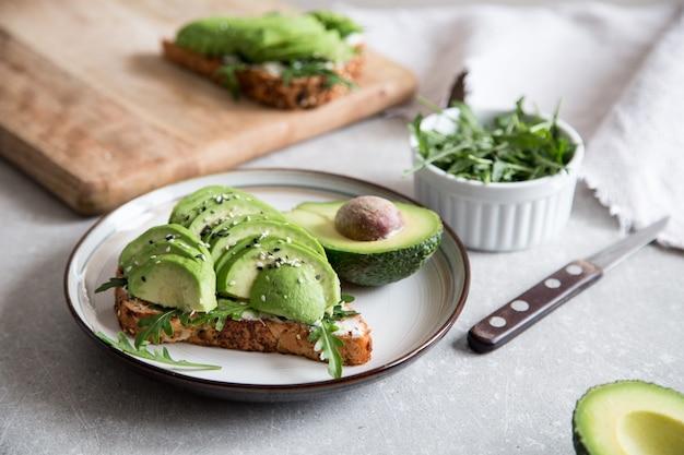 Gesundes frühstück mit avocado und köstlichem vollweizentoast.