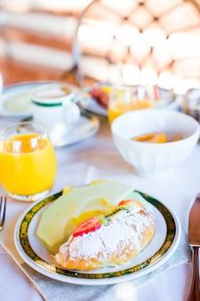 Gesundes frühstück mit frischem saft und süßem hörnchen im restauranterholungsort im freien