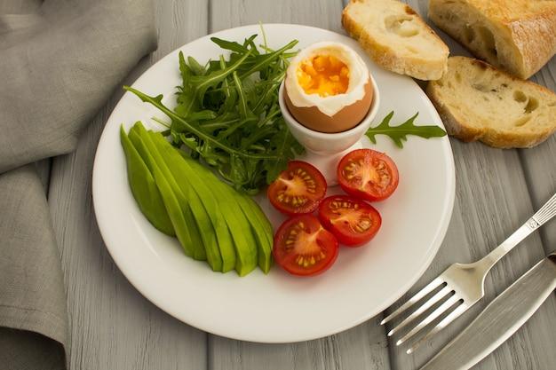 Gesundes frühstück mit gekochtem ei und gemüse auf dem weißen teller