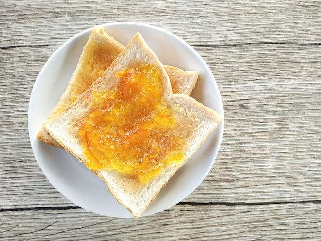 Gesundes frühstück mit geschmackvollen frühstückstoast (mit orangen- und ananasmarmelade) auf holztisch.