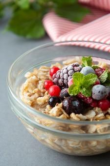 Gesundes frühstück mit hafer, beeren und minze. haferbrei mit früchten.