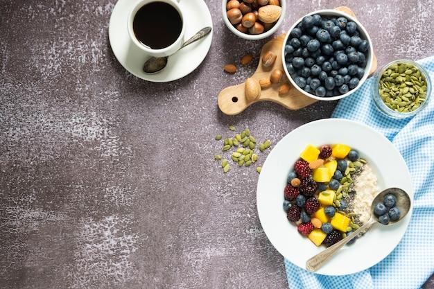 Gesundes frühstück mit haferbrei mit früchten und kaffeetasse.