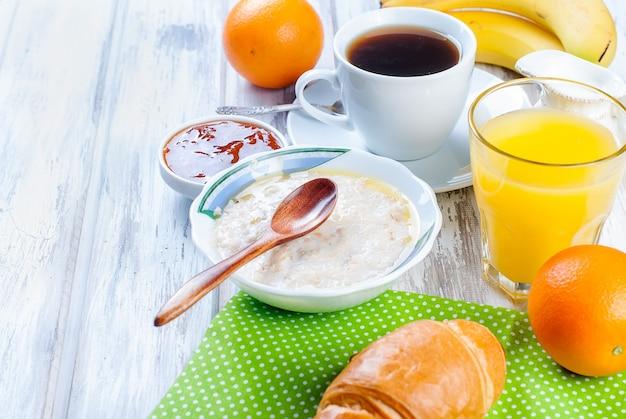 Gesundes frühstück mit haferflocken mit butter, croissant und kaffee