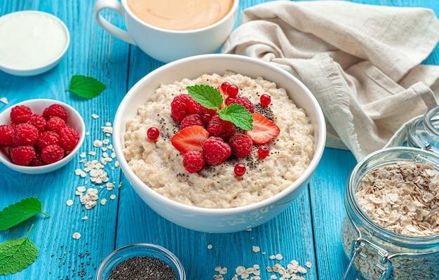 Gesundes frühstück mit haferflocken mit himbeeren erdbeeren rote johannisbeeren auf blauem hintergrund
