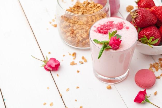 Gesundes frühstück mit joghurt, granola und erdbeeren auf weißem holz