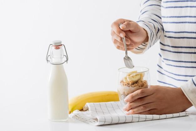 Gesundes frühstück mit joghurt, nuss, banane und chiasamen. schüssel mit frischem obst.