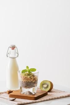 Gesundes frühstück mit joghurt, nuss, kiwi und chiasamen. schüssel mit frischem obst.