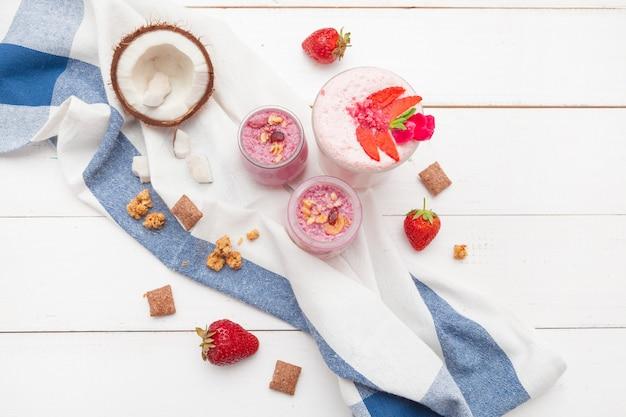 Gesundes frühstück mit jogurt, granola und erdbeeren auf weißer hölzerner draufsicht
