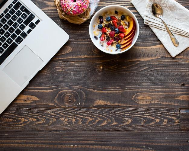 Gesundes frühstück mit milch, müsli und obst, auf einer holzoberfläche.