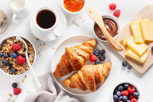 Gesundes frühstück mit müsli, beeren, nüssen, croissant, marmelade, schokoladenaufstrich und kaffee. draufsicht