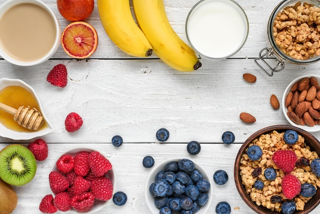 Gesundes frühstück mit müsli, früchten, beeren, cappuccino und nüssen auf weißem holztisch