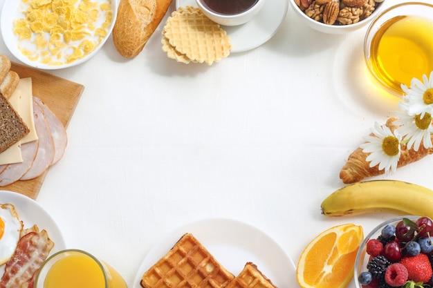 Gesundes frühstück mit müsli, früchten, beeren, nüssen, kaffee, eiern, honig, haferkörnern und anderem auf weißem hintergrund. flache lage, draufsicht, kopierraum für text, rahmen