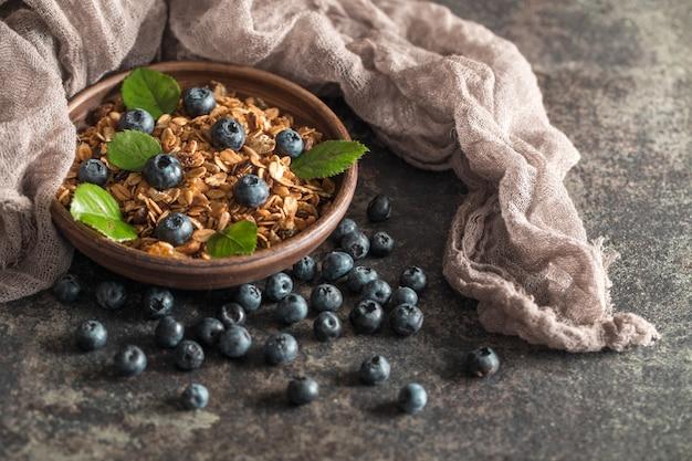 Gesundes frühstück mit müsli und beeren auf dunklem hintergrund