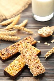 Gesundes frühstück mit müsliriegeln und milch auf braunem holztisch.