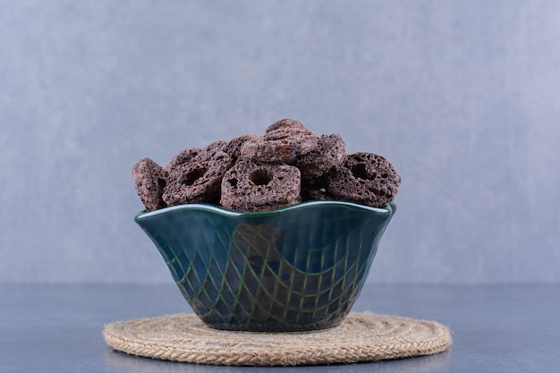 Gesundes frühstück mit schokoladenmaisringen in einem teller auf einem stein.