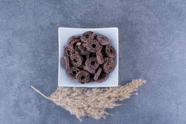 Gesundes frühstück mit schokoladenmaisringen in einem teller auf stein.