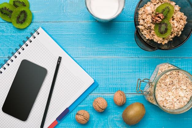 Gesundes frühstück mit schüssel hausgemachte haferflocken mit früchten und milch auf rustikalem holzhintergrund. stillleben. platz kopieren