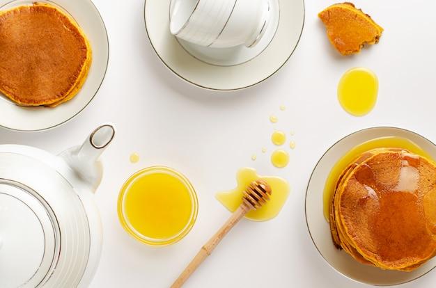 Gesundes frühstück mit selbst gemachten diätpfannkuchen und -honig auf weiß