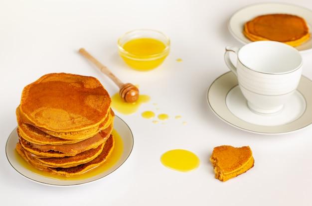 Gesundes frühstück mit selbst gemachten diätpfannkuchen und -honig auf weißem hintergrund