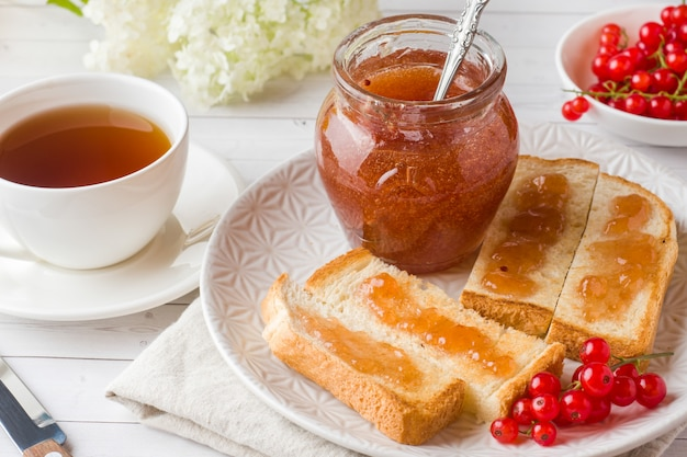 Gesundes frühstück mit toast, marmelade und roten johannisbeeren