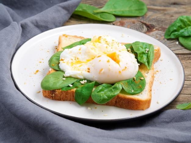 Gesundes frühstück mit toast und pochiertem ei mit grünem salat, spinat. seitenansicht.