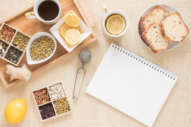 Gesundes frühstück mit verschiedenen kräutern; zitrone; sieb; brot; ingwer und leere spirale notizblock