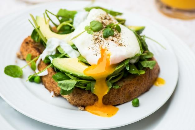 Gesundes frühstück mit vollkornbrot-toast und poschiertem ei