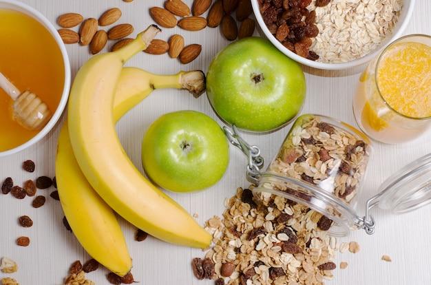 Gesundes frühstück. müsli, äpfel, bananen, haferflocken mit rosinen