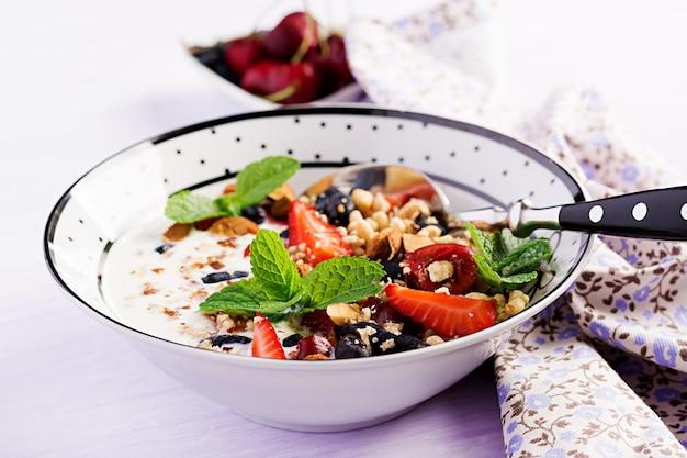 Gesundes frühstück - müsli, erdbeeren, kirsche, geißblattbeere, nüsse und joghurt in einer schüssel
