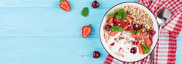 Gesundes frühstück - müsli, erdbeeren, kirschen, nüsse und joghurt in einer schüssel auf einem holztisch. vegetarisches konzeptessen. draufsicht