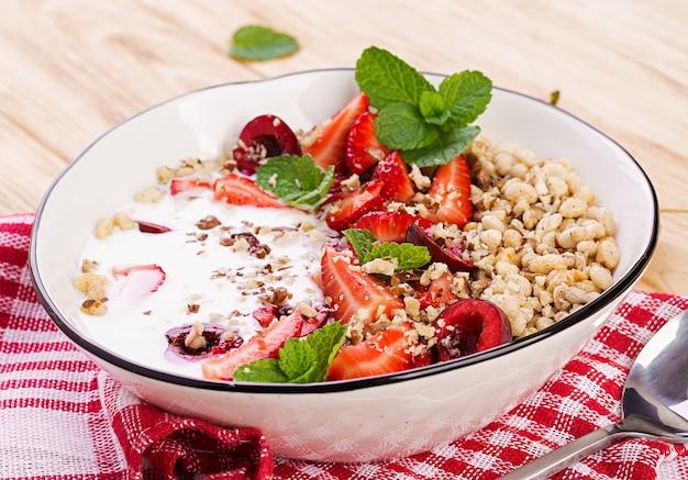 Gesundes frühstück - müsli, erdbeeren, kirschen, nüsse und joghurt in einer schüssel auf einem holztisch. vegetarisches konzeptessen.