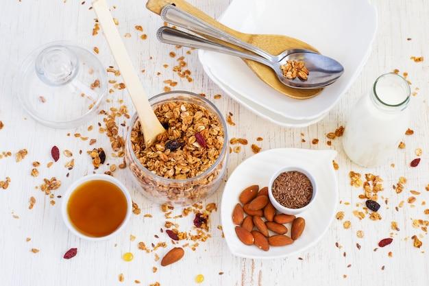 Gesundes frühstück. müsli, mandeln, milch, honig und eine schüssel