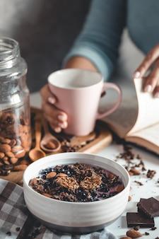 Gesundes frühstück, müsli mit beeren und orangensaft auf glastisch und büchern. maniküre
