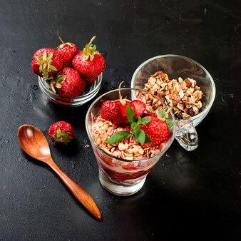 Gesundes frühstück. müsli mit erdbeeren, honig, nüssen,