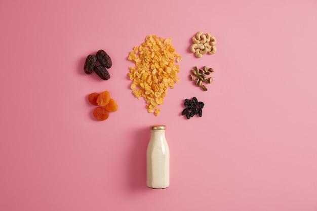 Gesundes frühstück müsli. müsli mit einer flasche frischer milch, getrockneten früchten und nährnüssen, um einen köstlichen, nahrhaften snack zuzubereiten, der den ganzen tag energie hat. diät und sauberes essen konzept.