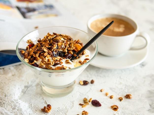 Gesundes frühstück. müsli, müsli mit kürbiskernen, honig, joghurt in einer glasschüssel