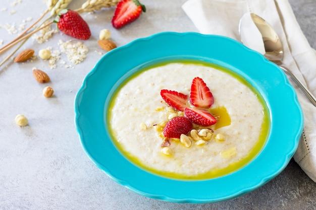 Gesundes frühstück nahaufnahme haferflockenbrei mit nüssen und frischen erdbeeren textfreiraum