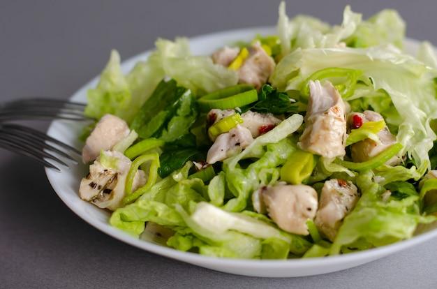 Gesundes frühstück oder mittagessen. frischgemüsesalat aus eisbergsalat, lauch und hähnchenbrust.