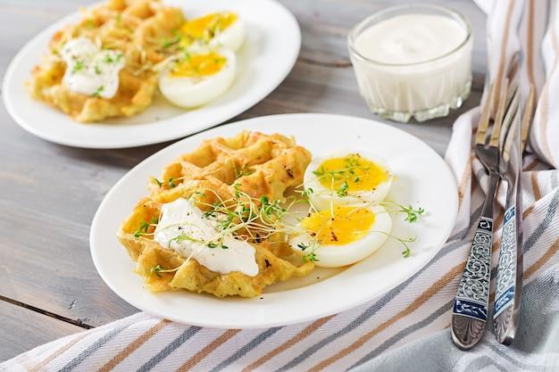 Gesundes frühstück oder snack. kartoffelwaffeln und gekochtes ei auf grauem holztisch.