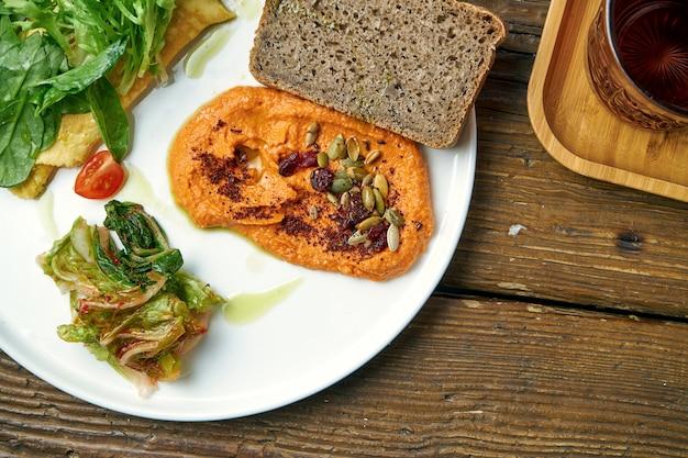 Gesundes frühstück - omelett mit kimchi und gebackenem paprika hummus in einem teller auf einem holz