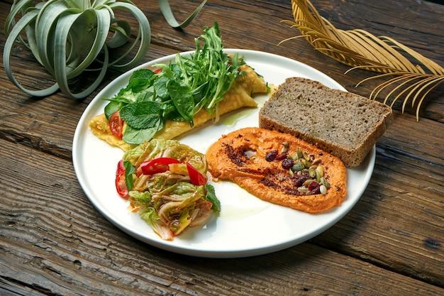 Gesundes frühstück - omelett mit kimchi und gebackenem paprika hummus in einem teller auf einem holztisch