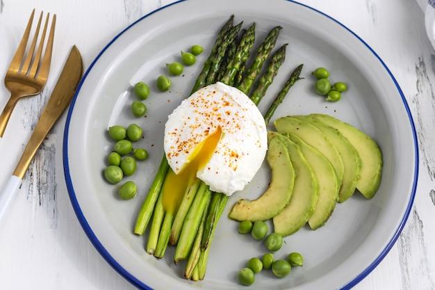 Gesundes frühstück - pochierte eier mit spargel, avocado und grünen erbsen