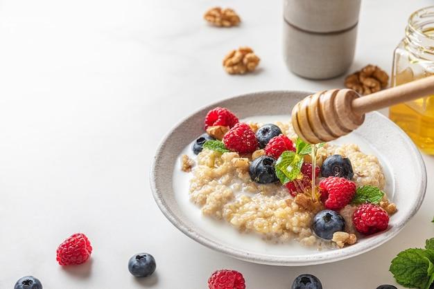 Gesundes frühstück. poring honig in einem teller mit quinoa-brei mit frischen beeren, nüssen und minze auf weißem hintergrund.