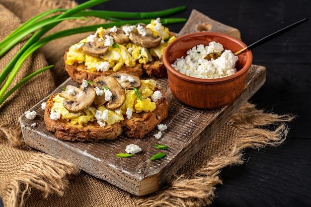 Gesundes frühstück. rührei mit pilzen und quark auf rustikalem toast mit pilzen. leckeres frühstück oder snack.
