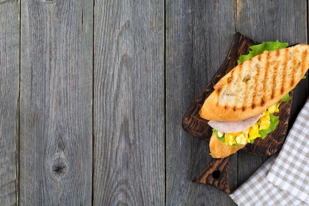 Gesundes frühstück. sandwich gefüllt mit rührei, schinken und salatblättern auf altem hölzernen hintergrund. draufsicht. selektiver fokus.