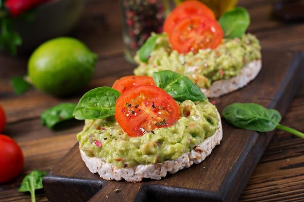 Gesundes frühstück. sandwich knäckebrot mit guacamole und tomaten auf einem holztisch.