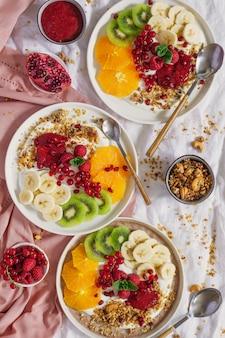 Gesundes frühstück. schüssel joghurt mit hausgemachtem müsli, marmelade und früchten.