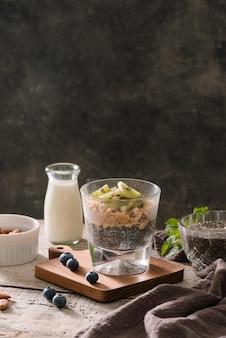 Gesundes frühstück - schüssel müsli, beeren und obst, nüsse, kiwi, milch