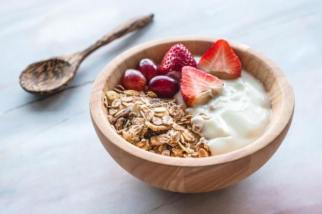 Gesundes frühstück. schüssel selbst gemachtes müsli mit joghurt und frischen früchten auf marmortabelle.
