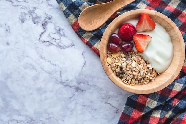 Gesundes frühstück. schüssel selbst gemachtes muesli mit jogurt und frischen früchten auf marmortabelle.